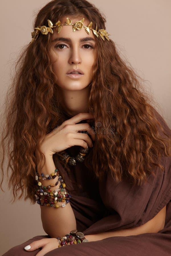 Mulher bonita Cabelo longo encaracolado Modelo de forma no vestido dourado Penteado ondulado saudável acessórios Autumn Wreath, c imagens de stock