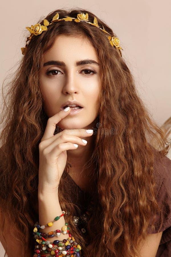 Mulher bonita Cabelo longo encaracolado Modelo de forma no vestido dourado Penteado ondulado saudável acessórios Autumn Wreath, c imagem de stock