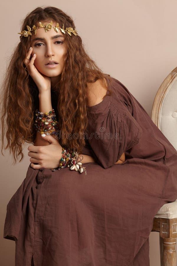 Mulher bonita Cabelo longo encaracolado Modelo de forma no vestido dourado Penteado ondulado saudável acessórios Autumn Wreath, c imagem de stock royalty free