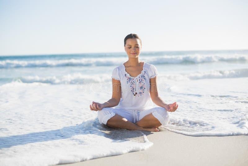 Mulher bonita calma na posição dos lótus sobre a praia com onda r imagens de stock royalty free