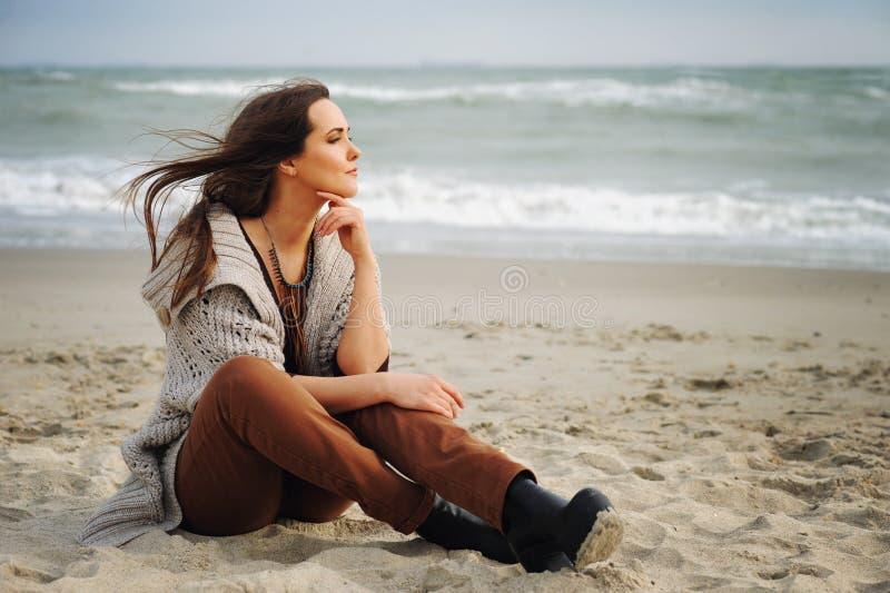 A mulher bonita calma senta-se apenas em uma areia da praia e olha-se a água fotos de stock