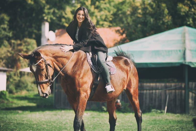 Mulher bonita a cavalo, tendo o divertimento com o cavalo no rancho imagens de stock royalty free
