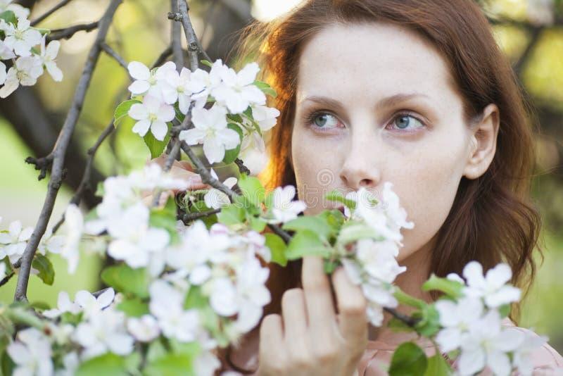 Mulher bonita com as flores brancas que olham afastado foto de stock