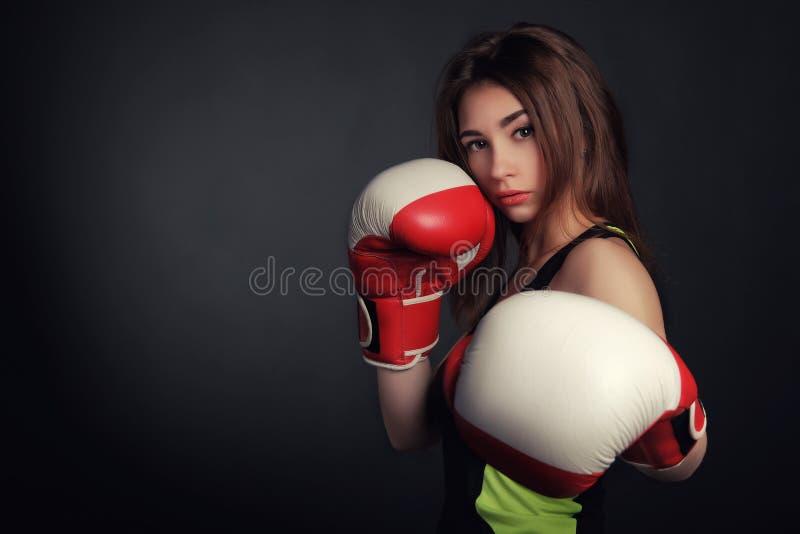 Mulher bonita com as luvas de encaixotamento vermelhas, fundo preto imagem de stock royalty free