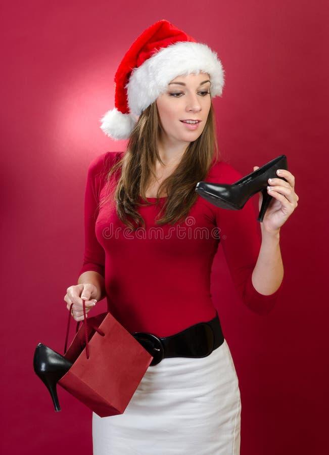 Mulher bonita com as sapatas da terra arrendada do chapéu de Santa imagem de stock