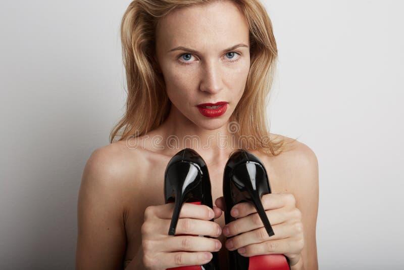 Mulher bonita com as sapatas em suas mãos fotos de stock