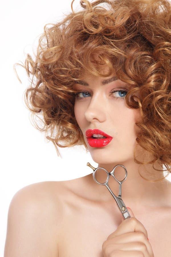 Mulher bonita com as tesouras do cabelo encaracolado e do cabeleireiro em sua mão fotografia de stock