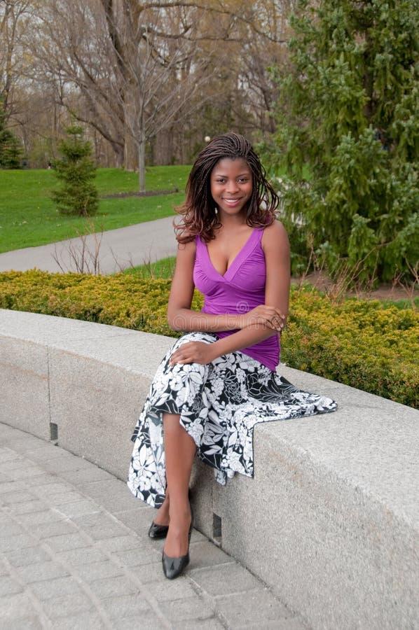 Mulher bonita com as tranças assentadas no parque foto de stock royalty free