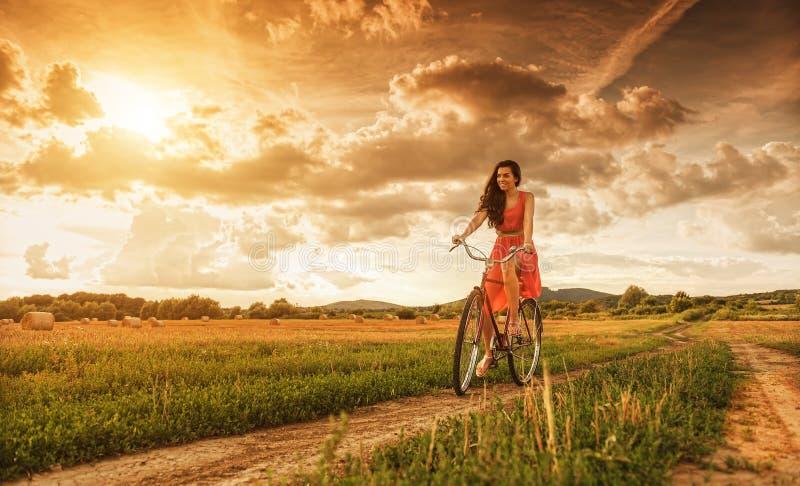 Mulher bonita com bicicleta velha em um campo de trigo fotos de stock royalty free