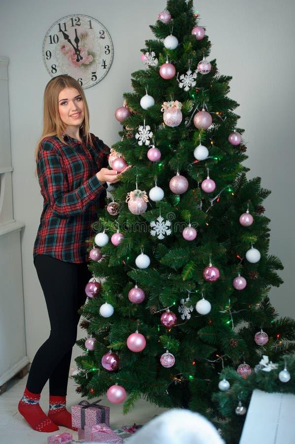 Mulher bonita com a bola do Natal perto de uma árvore de Natal H foto de stock