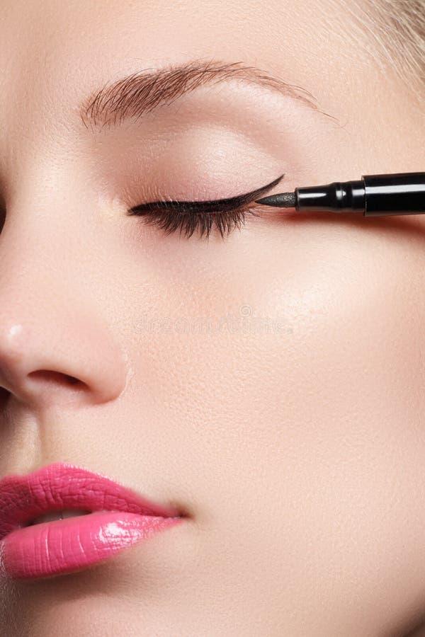 A mulher bonita com brilhante compõe o olho com a composição preta 'sexy' do forro Forma da seta da forma Composição chique da no fotografia de stock