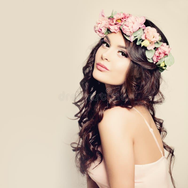 Mulher bonita com cabelo encaracolado, composição e flores fotografia de stock