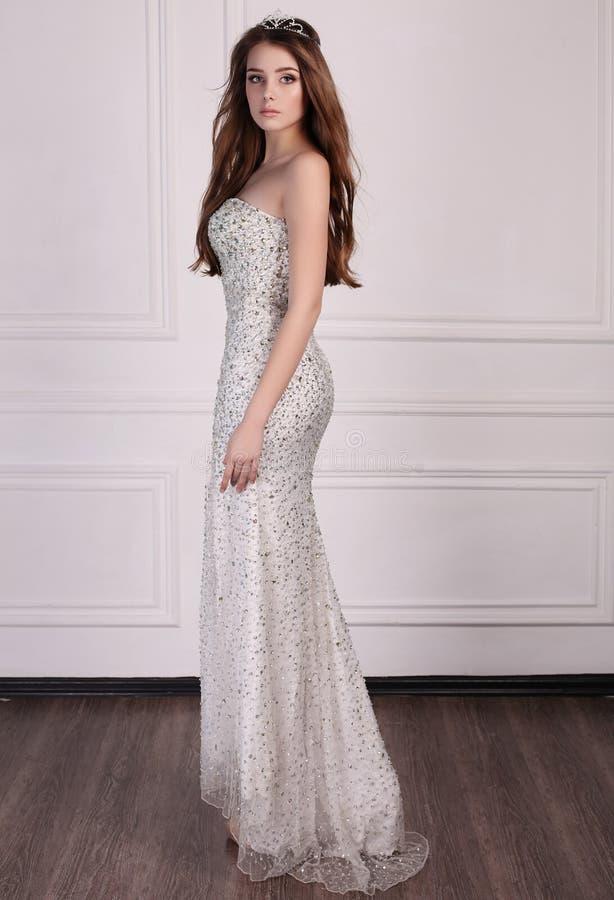 A mulher bonita com cabelo escuro veste o vestido elegante e a coroa preciosa imagens de stock royalty free