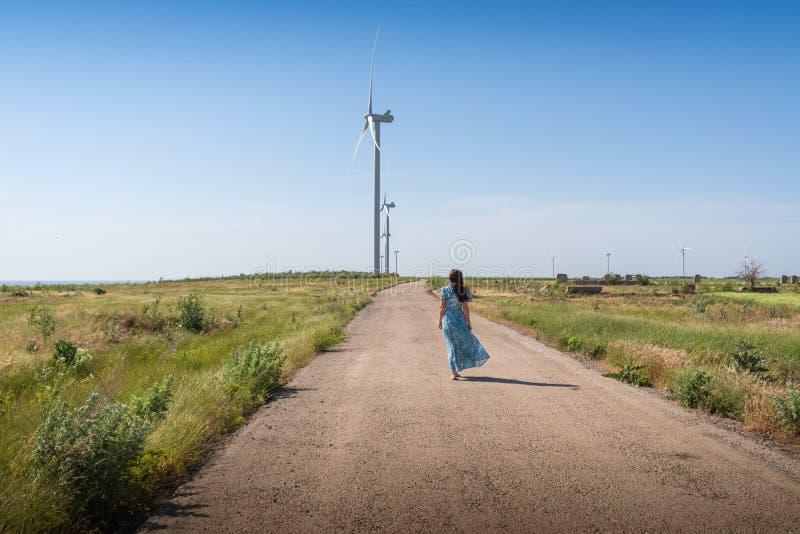 A mulher bonita com cabelo longo em um vestido azul anda na estrada entre campos e turbinas eólicas verdes no céu azul foto de stock royalty free