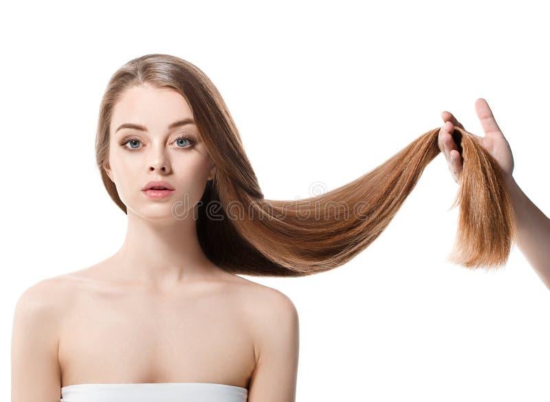 A mulher bonita com cabelo longo saudável mantém o cabelo disponivel com natureza para compor imagem de stock