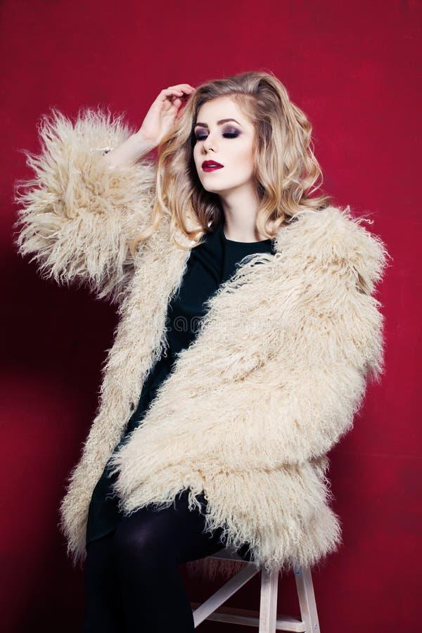 Mulher bonita com cabelo louro encaracolado no vermelho brilhante fotos de stock royalty free