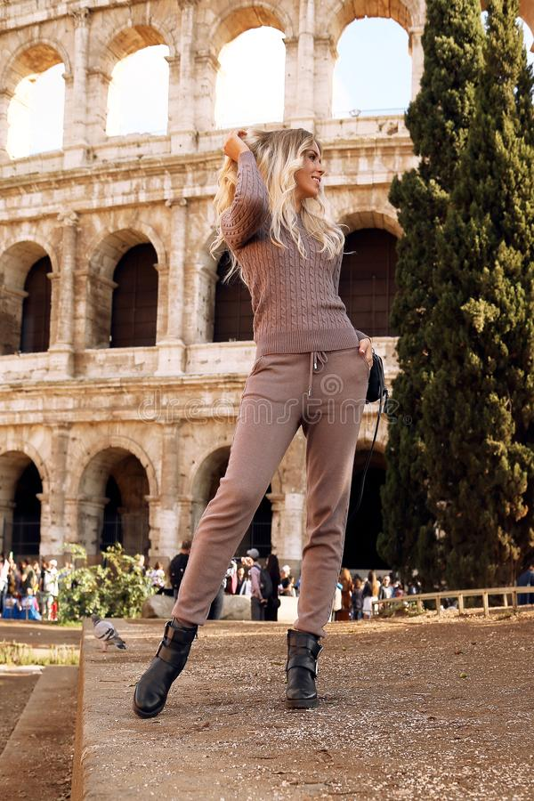 Mulher bonita com cabelo louro na roupa acolhedor ocasional que levanta perto de Colosseum em Roma fotos de stock royalty free