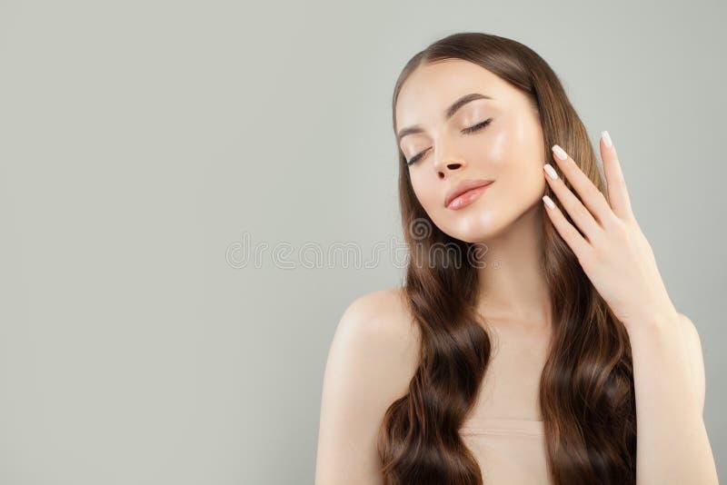 Mulher bonita com cabelo marrom saudável longo no retrato cinzento do fundo imagens de stock royalty free