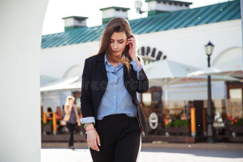 Mulher bonita com cabelo saudável longo Olhar do ` s das mulheres elegantes com revestimento preto e a blusa azul Conceito da for fotos de stock royalty free
