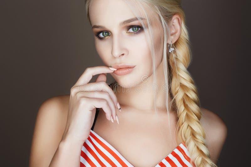 A mulher bonita com cabelo trançado, compõe e tratamento de mãos foto de stock royalty free