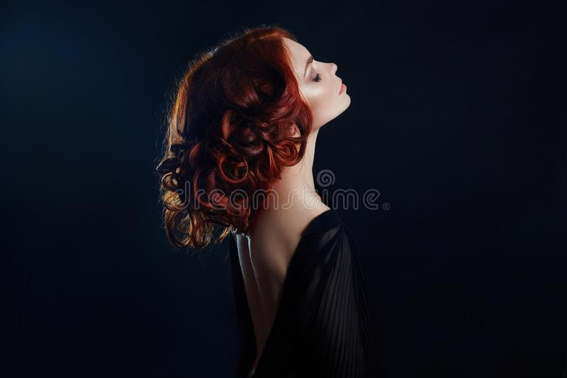 Mulher bonita com cabelo vermelho em um fundo preto Retrato de uma mulher bem sucedida, pele pura, composição natural, cara dos c imagem de stock