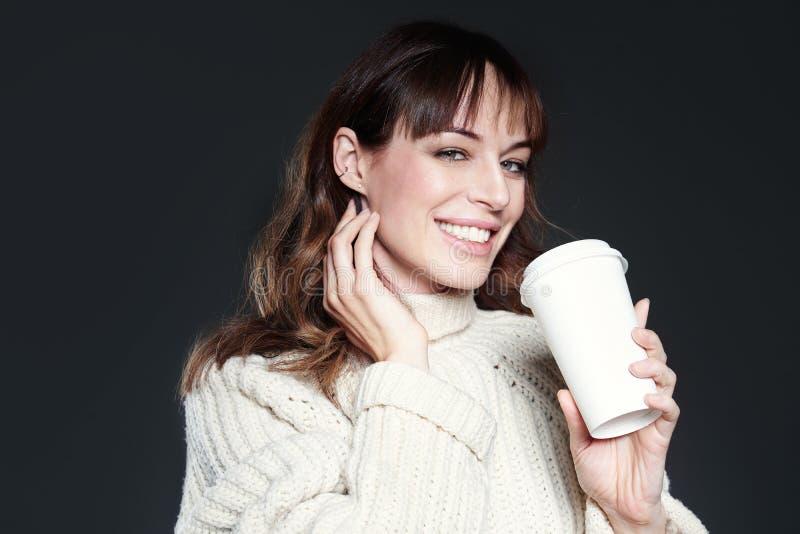 A mulher bonita com a camiseta vestindo do cabelo longo guarda o copo de café descartável de papel Café bebendo com a cara relaxa foto de stock royalty free