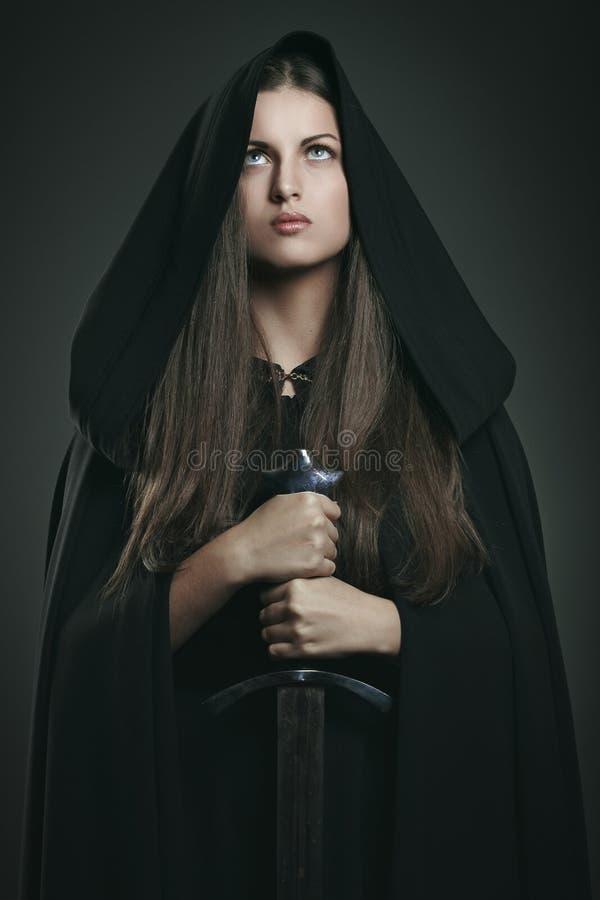 Mulher bonita com casaco e a espada pretos fotografia de stock royalty free