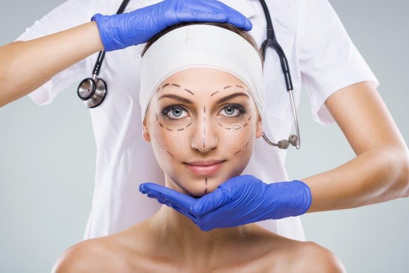Mulher bonita com cirurgia plástica, descrição, mãos do cirurgião plástico foto de stock