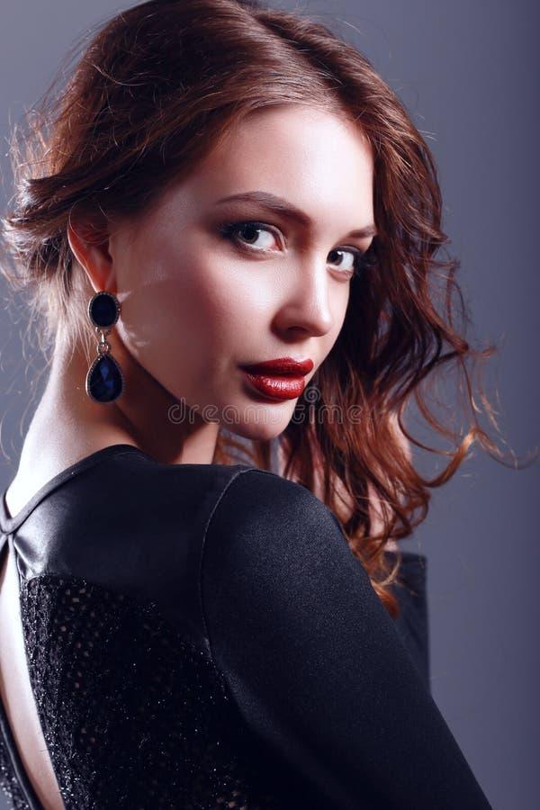 Mulher bonita com composição da noite no vestido preto fotografia de stock