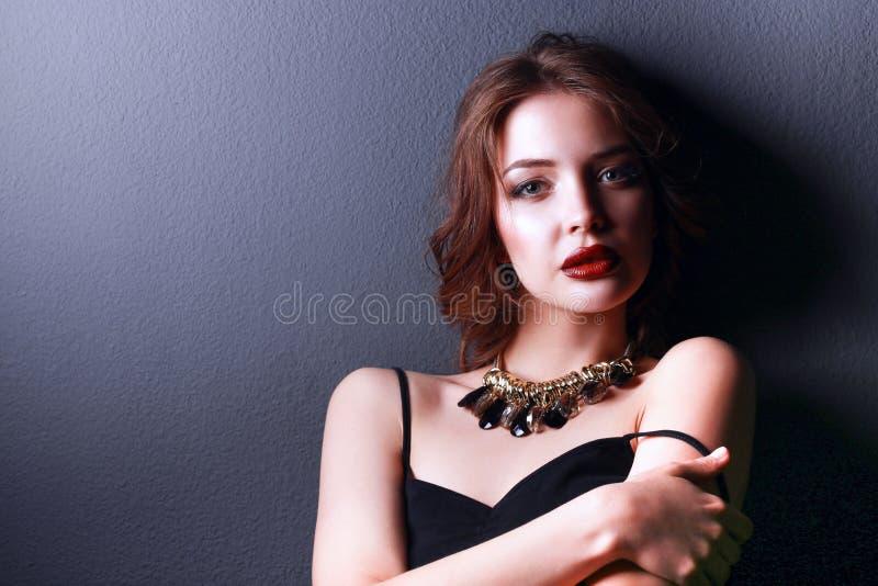 Mulher bonita com composição da noite no vestido preto foto de stock royalty free