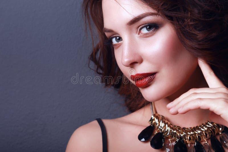 Mulher bonita com composição da noite no vestido preto imagem de stock royalty free