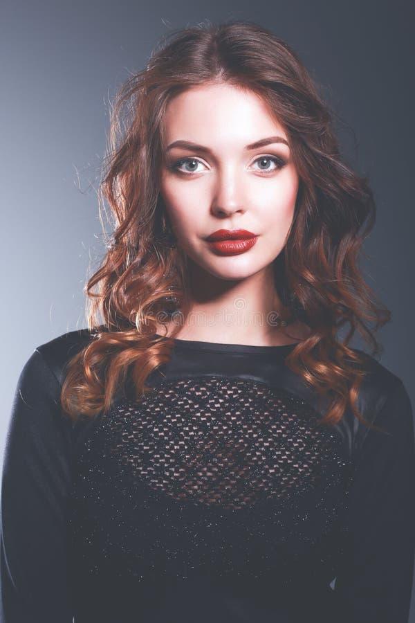 Mulher bonita com composição da noite no vestido preto imagem de stock