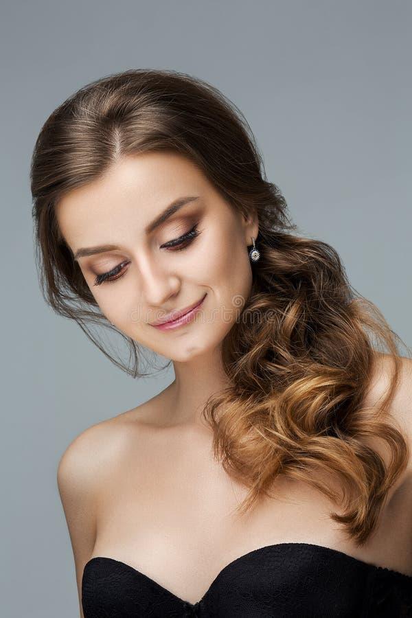Mulher bonita com composição e penteado sobre o fundo cinzento imagem de stock
