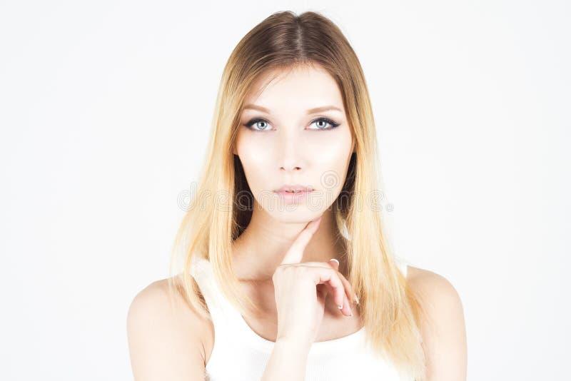 Mulher bonita com a composição permanente que guarda o dedo sob seu queixo fotografia de stock royalty free
