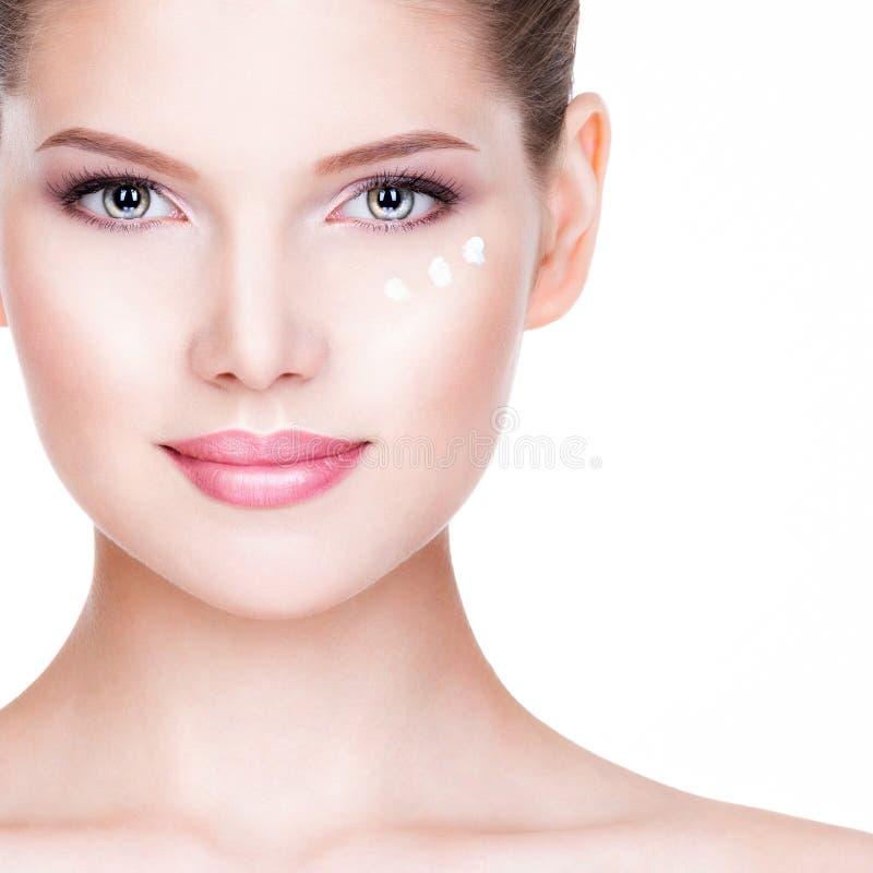 Mulher bonita com creme cosmético sob os olhos imagem de stock