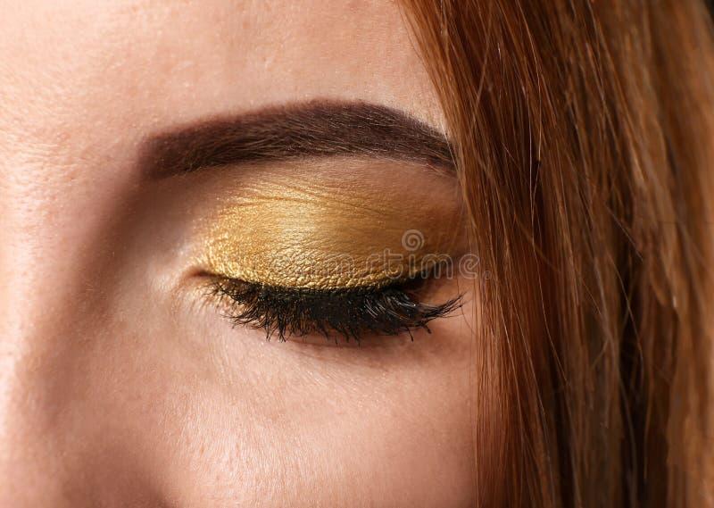 A mulher bonita com dourado compõe, close up fotografia de stock