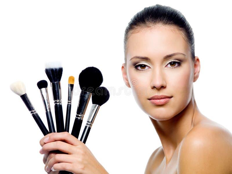 Mulher bonita com escovas da composição imagem de stock
