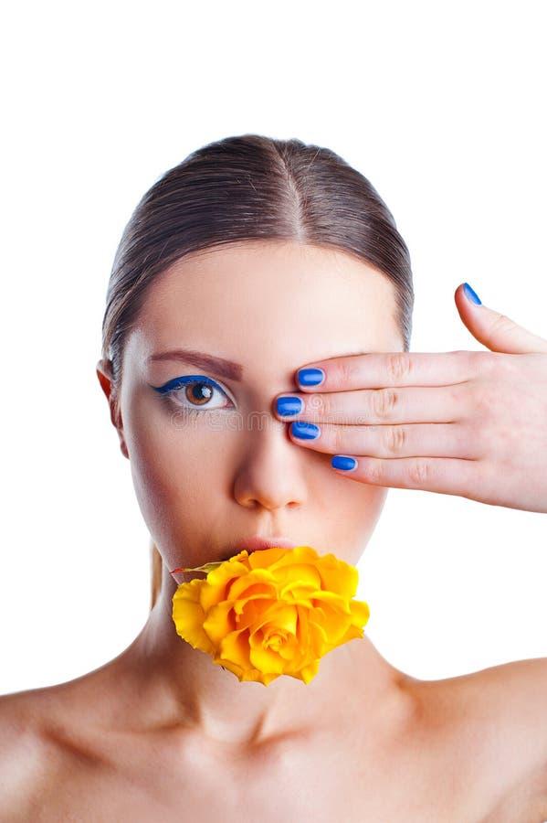 Mulher bonita com a flor da rosa do amarelo em sua boca fotos de stock