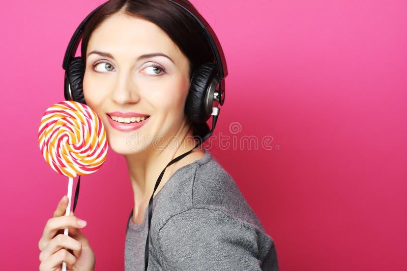 Mulher bonita com fones de ouvido e doces fotografia de stock royalty free