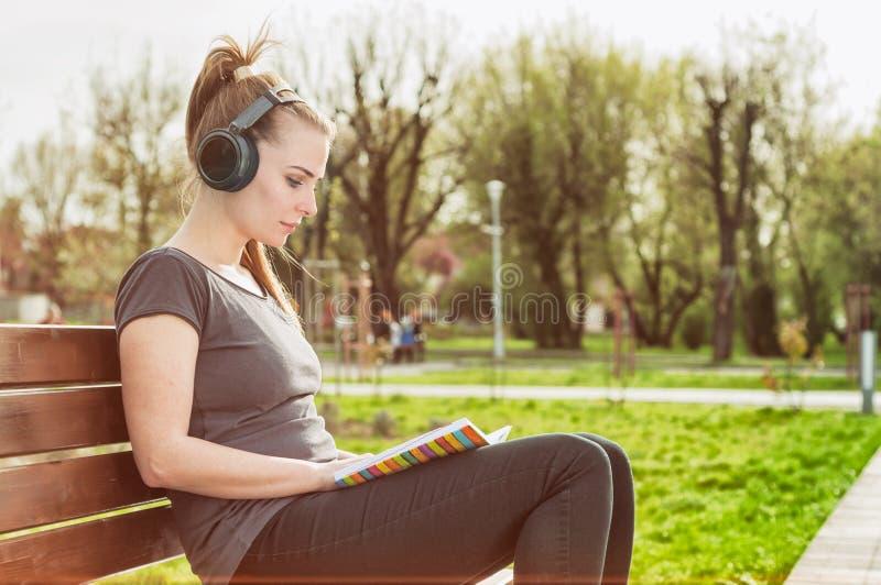 Mulher bonita com fones de ouvido que lê um livro no parque fotos de stock