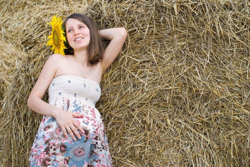A mulher bonita com girassóis aproxima o monte de feno - beleza e forma fotos de stock royalty free