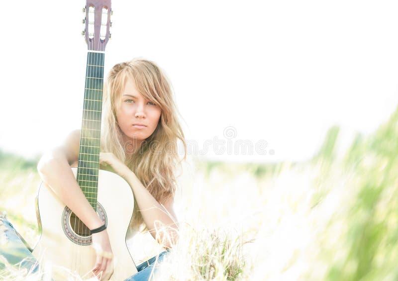 Mulher bonita com a guitarra que senta-se na grama. imagem de stock royalty free