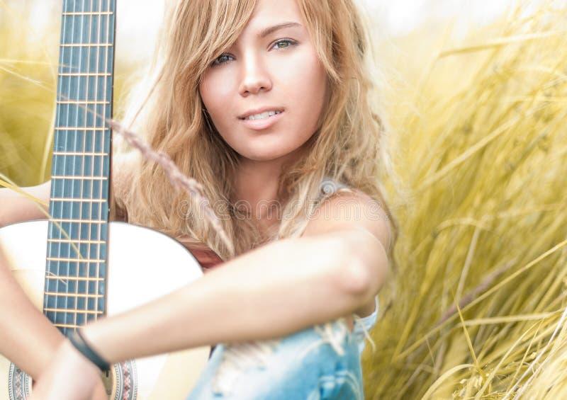 Mulher bonita com a guitarra que senta-se na grama. fotos de stock royalty free