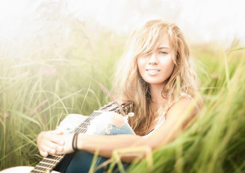 Mulher bonita com a guitarra que senta-se na grama. imagens de stock
