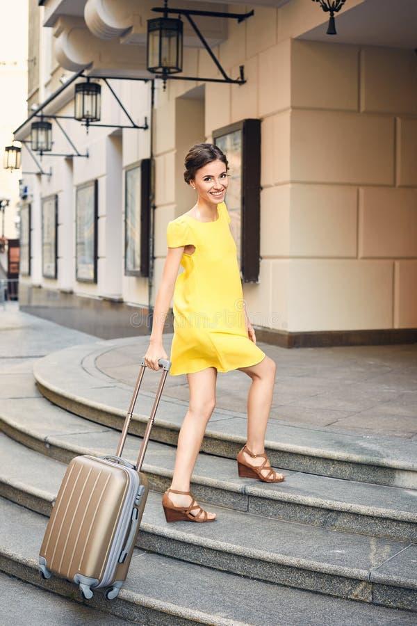 Mulher bonita com a mala de viagem na entrada ao hotel imagem de stock
