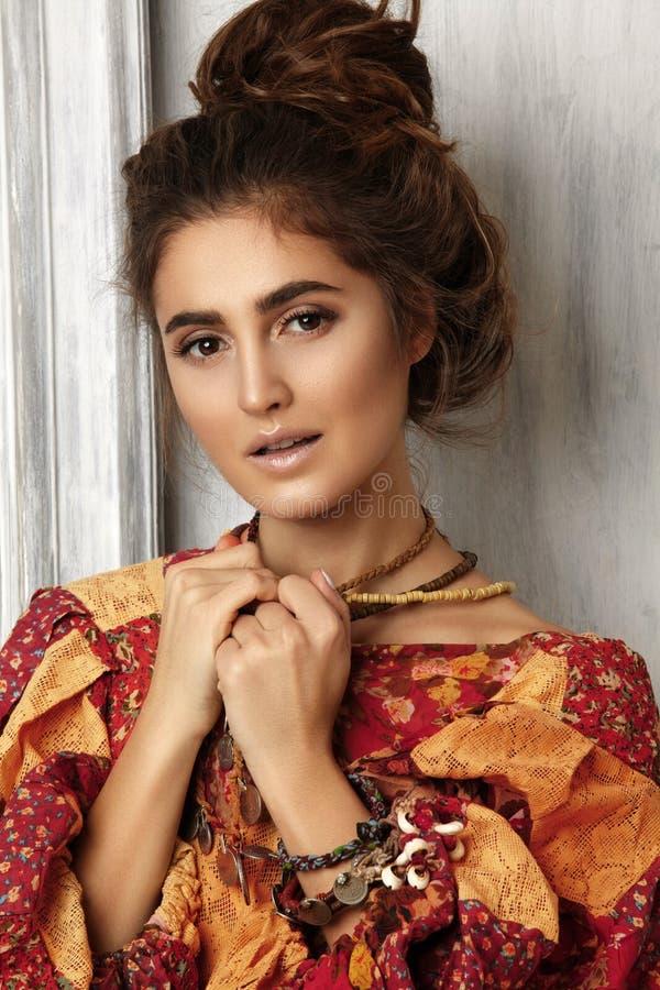 Mulher bonita com o bolo médio do penteado com cabelo de Brown Modelo 'sexy' em Autumn Color Dress Acessórios do estilo da hippie imagens de stock royalty free