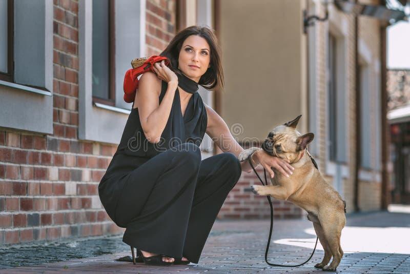 Mulher bonita com o cão na rua foto de stock