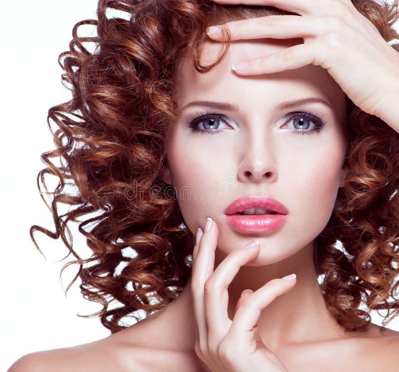 Mulher bonita com o cabelo encaracolado moreno que levanta no estúdio fotos de stock royalty free