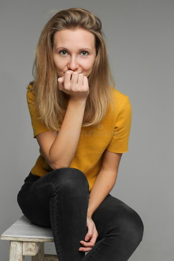 Mulher bonita com o cabelo justo completo que senta-se na cadeira no estúdio imagem de stock