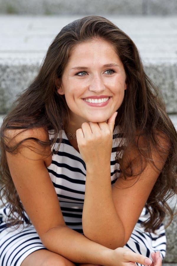 Mulher bonita com o cabelo longo que senta-se em escadas foto de stock royalty free